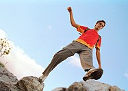 Young man stepping across rocks, low angle view