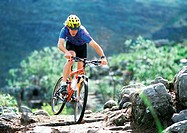 Young man on mountain bike, riding on mountain trail
