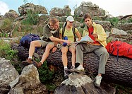 Three young hikers sitting on tree trunk, checking map