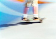 Man skateboarding, low section, blurred