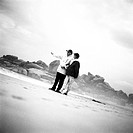 Mature couple standing on beach, man pointing, b&w
