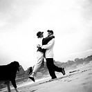 Mature couple and dog on beach, woman jumping into man's arms, b&w