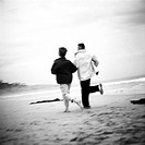Mature couple running on beach, rear view, b&w