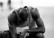 Male athlete crouching, head down, close-up, b&w (thumbnail)
