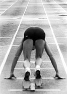 Male runner at starting block, rear view, b&w