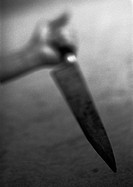 Hand holding kitchen knife, blurred, b&w