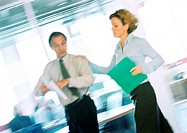 Man and woman walking in office, blurred