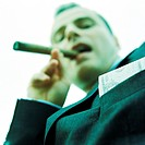 Businessman smoking cigar, low angle view, portrait