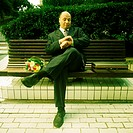 Businessman sitting on bench with bouquet of flowers, looking at watch (thumbnail)