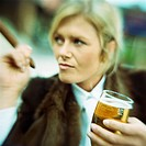 Businesswoman with beer and cigar, blurred, portrait