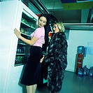 Woman in fur coat touching second woman's rear, second woman leaning against vending machine, side view