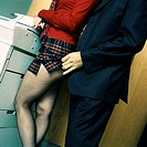 Woman standing at photocopy machine, man in suit lifting woman's skirt, mid-section
