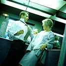 Businesswoman pulling businessman toward her by his tie, in elevator