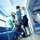 Three young women office workers surrounding male colleague