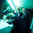Three businessmen in bathroom, two with hands on head, side view