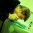 Man in suit sniffing cocaine in bathroom
