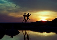 Couple running near water at sunset, silhouette