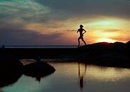 Woman running near water at sunset, silhouette