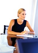 Businesswoman sitting at desk (thumbnail)