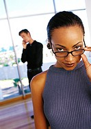 Businesswoman lowering glasses, man talking on phone in background, portrait