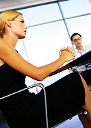 Businessman and woman sitting in office, low angle view