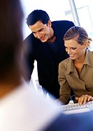 Businessman and woman using computer, smiling