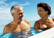Mature couple smiling in swimming pool