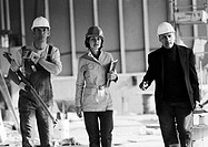 Two men and woman wearing hard hats, b&w