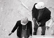 Two people wearing hard hats, elevated view, b&w