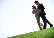 Businessman and woman with cell phone, walking on grass