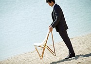 Businessman holding chair on beach