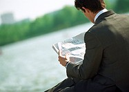 Businessman reading newspaper, outdoors, rear view, tilt