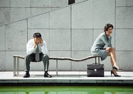 Businessman and woman on bench, using cell phones