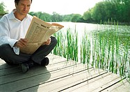 Man sitting outdoors, reading newspaper
