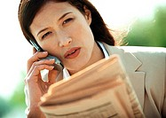 Businesswoman using cell phone, close-up, tilt