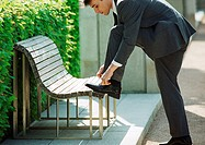 Businessman tying shoelaces on bench