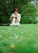 Woman sitting on grass, reading book