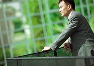 Businessman leaning on railing, close-up