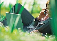 Businesswoman lying on grass with laptop and cell phone