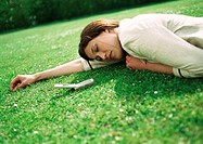 Businesswoman lying on grass with cell phone near head