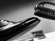Brush above leather shoe, close-up, b&amp;w