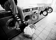 Person sitting on washing machine in laundrymat, low section, b&amp;w