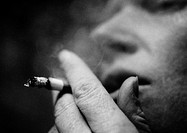 Person smoking cigarette, close-up, blurred, b&amp;w