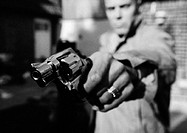 Man holding gun, close-up, b&amp;w