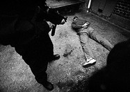 Man standing and pointing sub-machine gun at man face-down on floor, b&amp;w