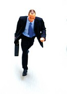 Businessman walking with briefcase in hand, elevated view