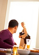 Man sitting at table looking at woman