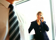 Businesswoman on phone, businessman's chest in foreground, close up