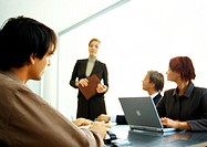 Business people around table looking at businesswoman standing