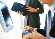 Businesswoman standing near businessman using computer, partial view